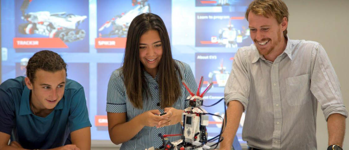 Three high school students are studying in the school library together.